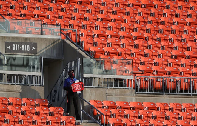 A security guard holds a face mask sign before a game last season at FirstEnergy Stadium in Cleveland.