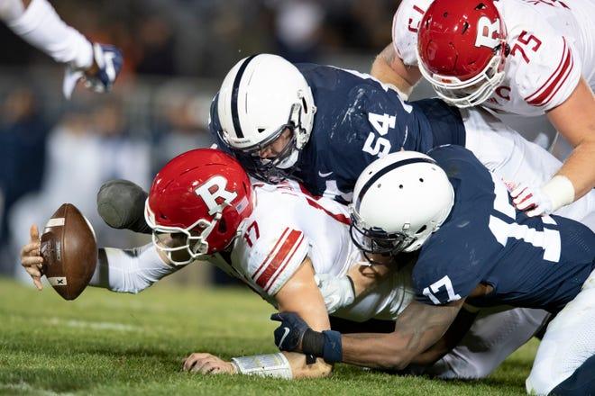 Penn State defenders Robert Windsor, 54, and Garrett Taylor, 17, force Rutgers quarterback Johnny Langan to fumble during a 2019 game.