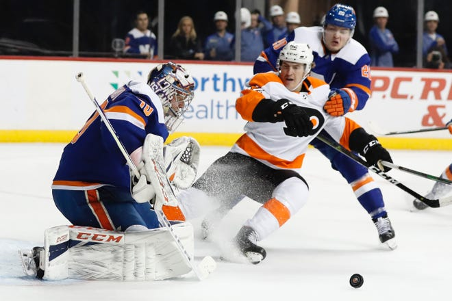 The Islanders' Semyon Varlamov makes the save as the Flyers' Nicolas Aube-Kubel closes in during a February game.