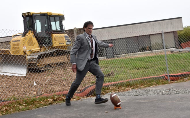 Lou Kassa, executive vice president of the Pennsylvania Biotechnology Center, prepares to kick a football through a ceremonial goalpost during the Thursday celebration of the center's $19 million expansion project.
