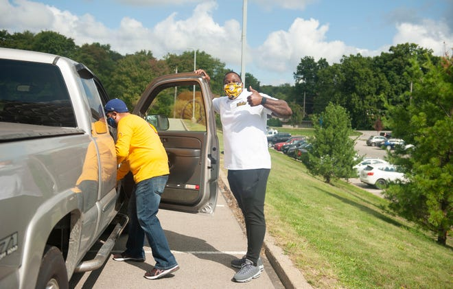 Former Steeler Arthur Moats, right, gives a thumbs up during a food distribution Friday morning in the parking lot of the Community College of Beaver County. Thousands of bags were donated by Shell Polymers and the Pittsburgh Steelers for individuals and families in need. Eddie Arreola, health, safety and environmental manager at Shell, left, loads a vehicle with supplies.