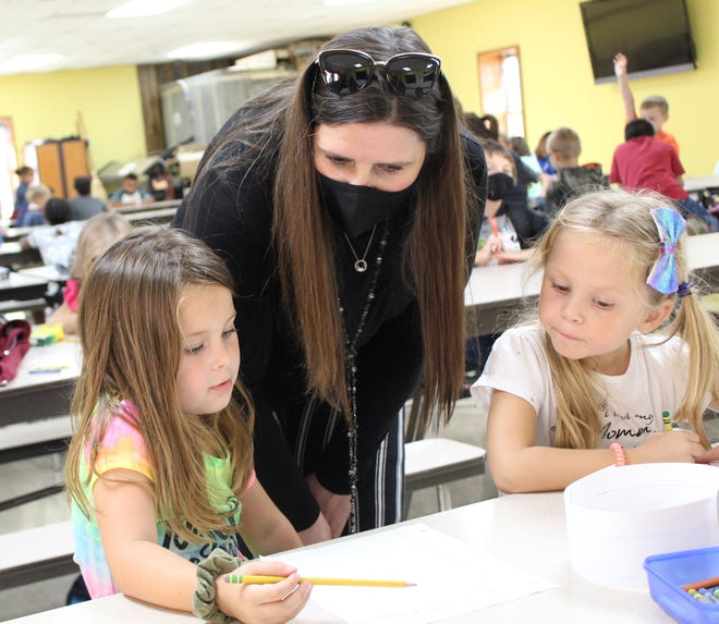 SLAM coordinator Kacy Medlin provides homework help to Caney Valley elementary kindergarteners Lynnden Diaz and Cambree Hyde.