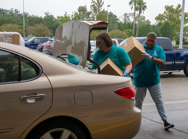 Kristen Hernandez puts food in a trunk while Taylor Boudoin waits with a box during the last food distribution at the Houma-Terrebonne Civic Center on Sept. 18.