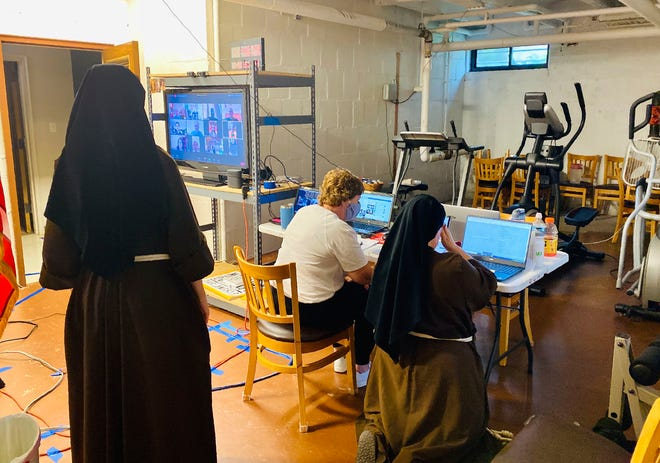 In this Aug. 23, 2020 photo, nuns from Mission of Our Lady of the Angels church monitor the livestream of Sister Stephanie Baliga running a marathon on a treadmill in Chicago.