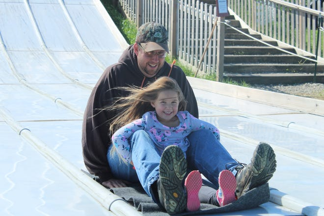 Hailey Kuczynski, 5, goes down a slide at Ramseyer Farm with her father Tim Kuczynski, of Lafayette Township.
