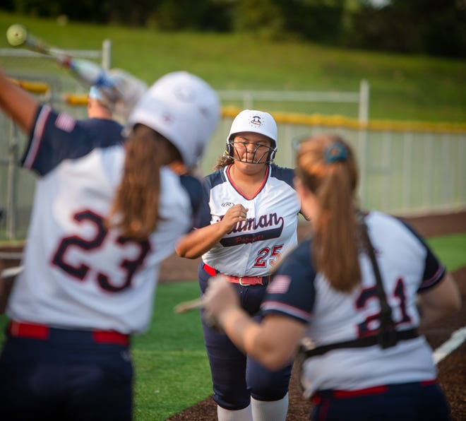 Truman pitcher Myel White, center, is greeted at home plate by teammates after slugging a two-run homer in the fifth inning of Thursday's game at Chrisman. White's blast keyed a four-run outburst as the Patriots went on to an 8-0 conference win over the crosstown rival.