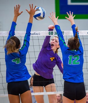 Blue Springs junior outside hitter Chloe Kaminski (4), hitting a spike against a block attempt by Blue Springs South's Kyla Braden (4) and Tori Valentine (12) in last year's match, has already verbally committed to Oklahoma.