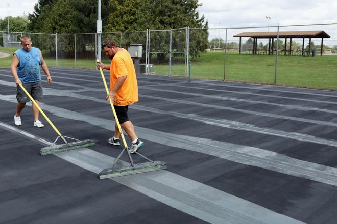 Chad Carter, left, and Jacob Robertson, with All Weather Courts of Dawson, Illinois, work on seam blending Friday as they resurface the Dankwardt Park tennis courts in Burlington. According to the Burlington Parks and Recreation Facebook post the project was made possible through a donation by the Starker Memorial Trust Fund and fundraising done by Brian Japsen and the Burlington Tennis Association.