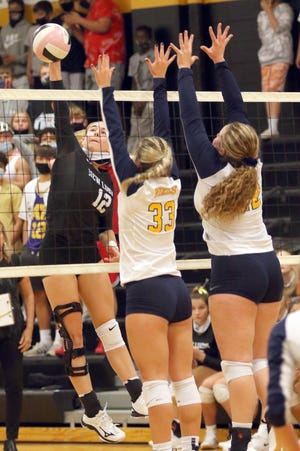 New London Tiger's Paris Wilka (12) pounds a kill past Notre Dame's Karli Artman (33) and Maisey Belger (22) Thursday at Charles Lorber Gymnasium in New London. [Donald K. Aliprandi/thehawkeye.com]