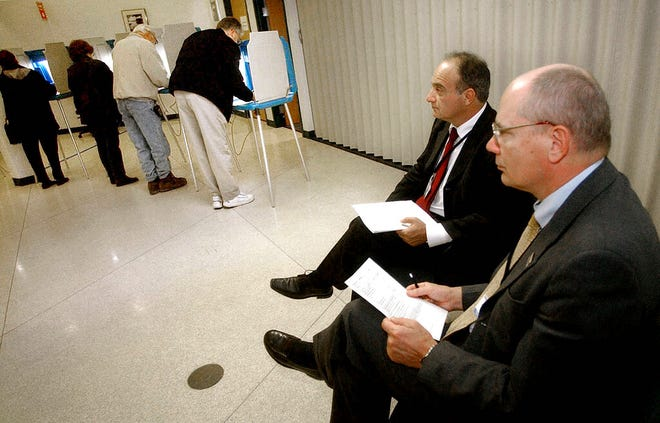 In this Nov. 2, 2004, file photo, parliamentarians Goran Lennmarker, right, of Sweden and Stavros Evagorow, of Cyprus, observe the American voting process as voters cast their ballots at Robbinsdale City Hall in Robbinsdale, Minn. The two men are members of the Organization for Security and Cooperation in Europe. Officials said Friday, Sept. 18, 2020, that due to the coronavirus pandemic, the security organization had drastically scaled back plans to send up to 500 observers to the U.S. to monitor the Nov. 3 presidential election, and now will deploy just 30.