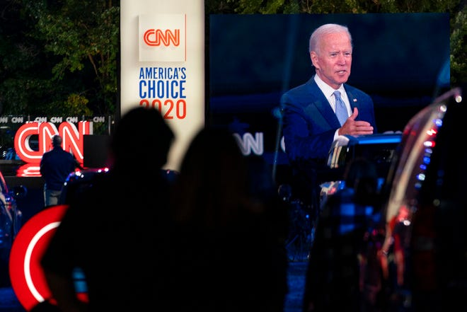 Audience members watch from their cars as Democratic presidential candidate former Vice President Joe Biden, seen on a monitor, speaks during a CNN town hall in Moosic, Pa., Thursday.