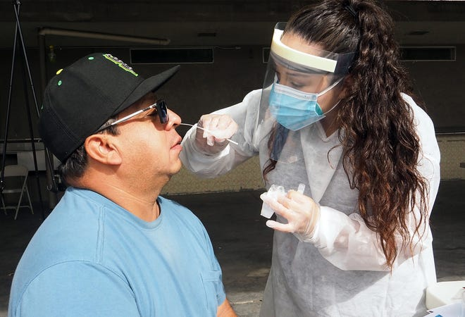 Claudia Quevzada of Trident Care gives a COVID-19 test to Juan Miranda during a free testing event that runs through the weekend at the San Joaquin County Fairgrounds.