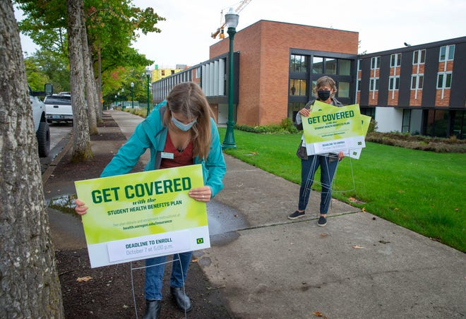 University of Oregon staff with the University Health Center, Shannon Millington, left, and Becki Penrod distribute signs for the Student Health Benefits Plan around campus in anticipation of the arrival of students this weekend as classes are set to begin later this month.
