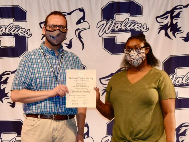 SHS Junior DeNiesha Barkus (right) receives her NHS certificate from Adviser Scott Bartley. More than 50 students were recently inducted into the school's NHS chapter.