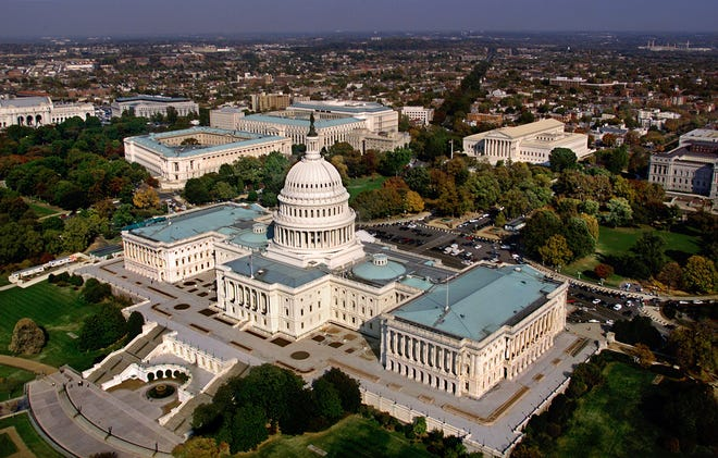 The Capitol in Washington, D.C. is shown in an aerial view. The view shows the west side of the Capitol, with the Senate to the left of the dome and the House of Representatives at the right.