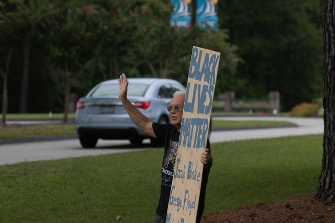 Craig Rosindale waves to passing cars at he holds up a Black Lives Matter sign at the entrance of Fairfield Harbour. [Bill Hand / Sun Journal Staff]