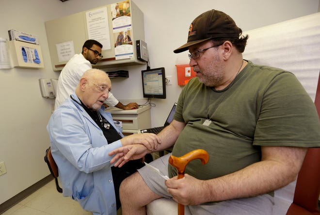 A doctor talks with an uninsured patient in 2017 in Cutler Bay.