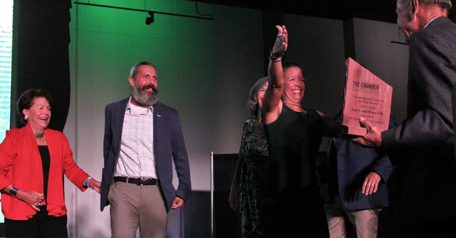 Marla Gill Ferguson, center, surprises her father, Larry (holding plaque at Thursday evening's Abilene Chamber of Commerce banquet, at which Larry and Mary Gill (far left) were honored as Outstanding Citizens of the Year. Their family joined them on stage, including son MIchael, to Mary Gill's left.