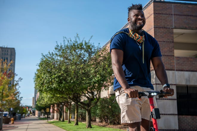 Odell Miller cruises through downtown Battle Creek on an electric Fly scooter on Thursday, Sept. 17, 2020. The former WMU football player is launching an electric scooter rental company for downtown Battle Creek and Kalamazoo.