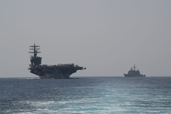 The aircraft carrier USS Nimitz, left, and the guided-missile cruiser USS Philippine Sea steam in formation during a Strait of Hormuz transit back on Sept. 18. On Sunday, the Pentagon ordered the Nimitz to say in the Middle East region.