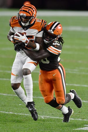 Sep 17, 2020; Cleveland, Ohio, USA; Cleveland Browns cornerback Tavierre Thomas (20) tackles Cincinnati Bengals wide receiver Tee Higgins (85) during the second half at FirstEnergy Stadium.
