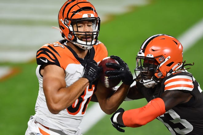 Sep 17, 2020; Cleveland, Ohio, USA; Cincinnati Bengals tight end C.J. Uzomah (87) catches a touchdown over the defense of Cleveland Browns defensive back Ronnie Harrison (33) during the first half at FirstEnergy Stadium.