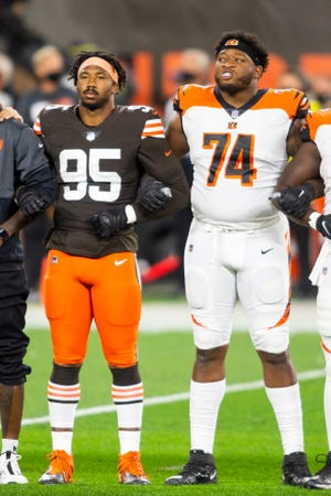 Sep 17, 2020; Cleveland, Ohio, USA; Cleveland Browns defensive end Myles Garrett (95) and Cincinnati Bengals offensive tackle Fred Johnson (74) lock arms during the national anthem at FirstEnergy Stadium.