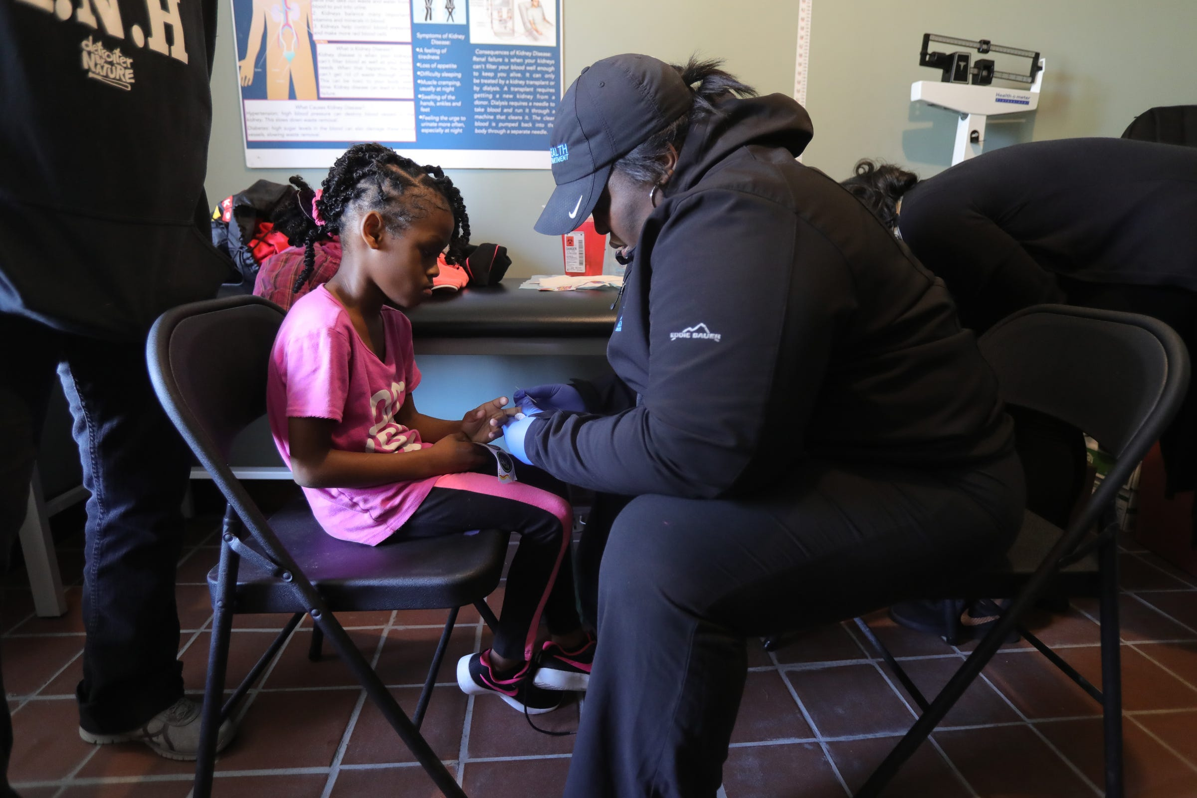 Ashleigh Adams, a city health department employee, tests the lead levels of Lyriq Wilson during a community bazaar put on by Sonia Brown, also known as Auntie Na, on Saturday, Oct. 19, 2019 in Detroit.