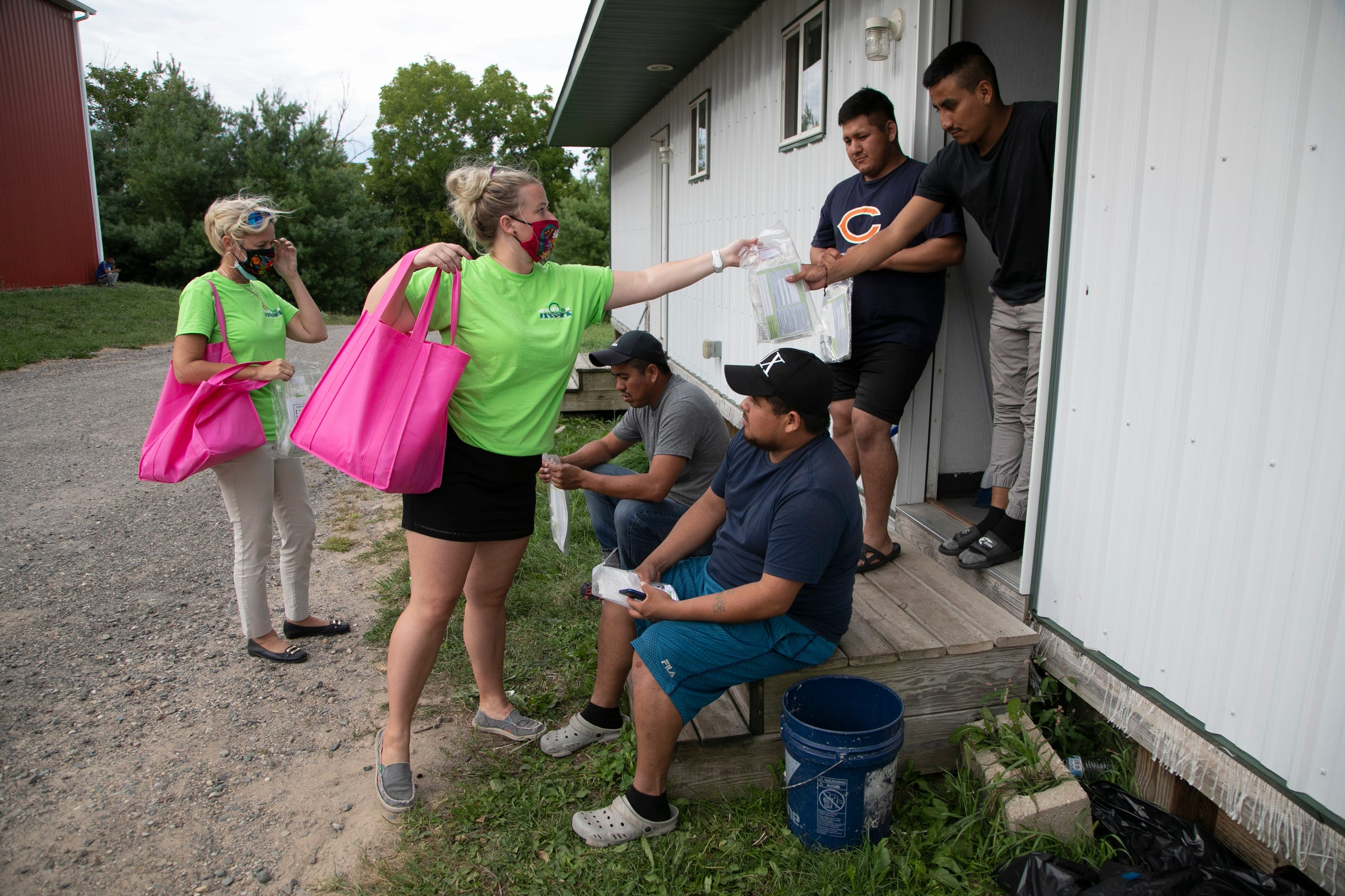 Migrant Legal Aid Executive Director Teresa Hendricks, left, and law clerk Molly Spaak hand out bags of face masks, hand sanitizer and gloves at a migrant camp in Kent County on Monday, Aug. 31, 2020.
