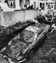 Workmen remove a 1974 Ferrari that was found buried in the backyard of a South Los Angeles home. The car had been reported stolen in 1974. Photograph dated February 7, 1978.