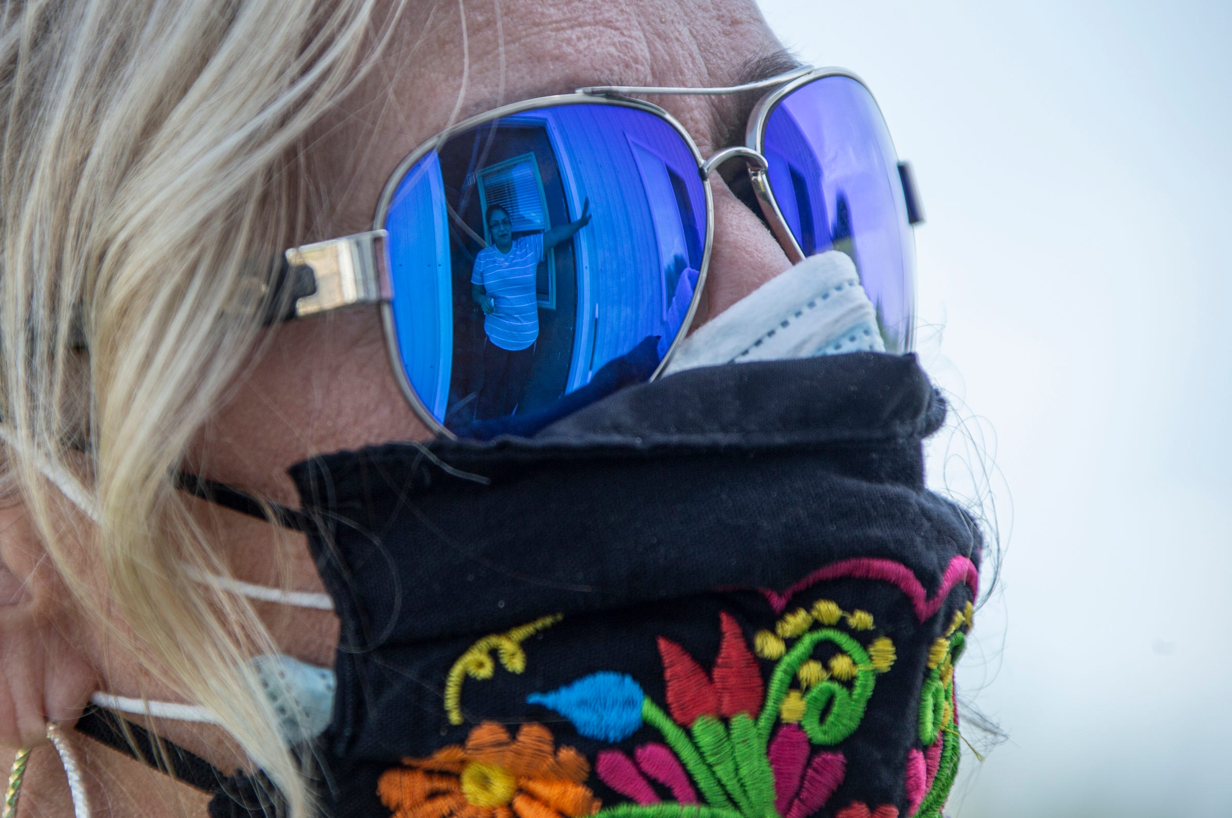 Brenda Martinez, 32, the wife of a farmworker, is reflected in the sunglasses of Migrant Legal Aid Executive Director Teresa Hendricks on Monday, Aug. 31, 2020 as Hendricks speaks to Martinez about COVID-19.