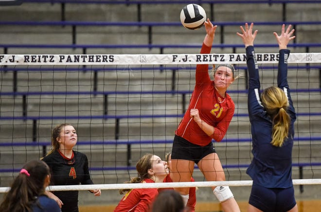 Mater Dei's Rachel Luigs (21) hits the ball over the net past defense from Reitz's Ashley Danks (7) as the Reitz Lady Panthers host the Mater Dei Wildcats Thursday, September 17, 2020.