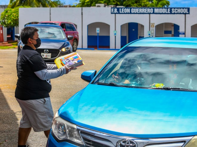 F.B. Leon Guerrero Middle School school aide Jovina Binondo delivers hard-copy resource material at the school during a drive-through distribution in this Sept. 18 file photo.