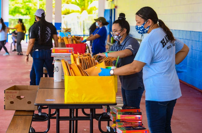 Teachers, school aides and other faculty members of F.B. Leon Guerrero Middle School in Yigo collect, exchange and distribute hard-copy resource material with visiting parents of students enrolled at the school in this Sept. 18 file photo.