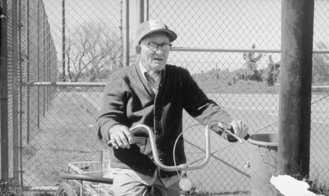 """Doc"" Hosbach, then age 74, sits on his yellow bike by the Water Street tennis courts that are named in his honor on September 1974."