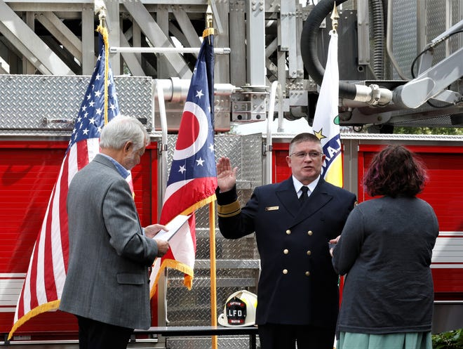 Steve Maffin is sworn in as the new assistant chief of the Lancaster Fire Department by Mayor David Scheffler, left, as his daughter Riley Maffin holds the Bible for him Friday, Sept. 18. Maffin joined LFD in 1994.