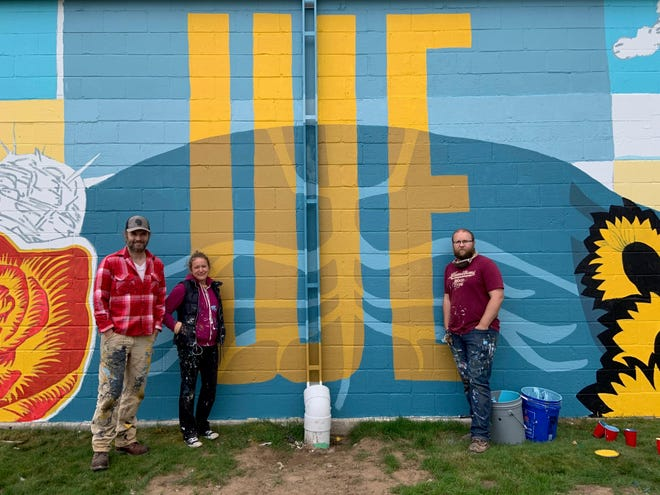 Artists Don Krumpos, Erin LaBonte and David Carpenter in front of a new mural on the Lakeside Foods building in Manitowoc.