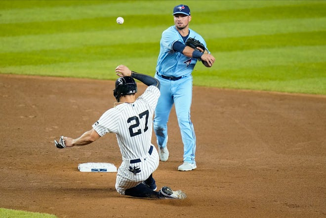 Toronto Blue Jays' Joe Panik throws out New York Yankees' Gleyber Torres at first base after forcing out Giancarlo Stanton, left, for a double play during the first inning of a baseball game Thursday, Sept. 17, 2020, in New York. The Yankees won 13-2.