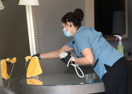 Room attendant Linda Briseno cleans a phone in a guest room at the Phoenician Aug 18, 2020. The resort has made changes in response to the COVID-19 outbreak.