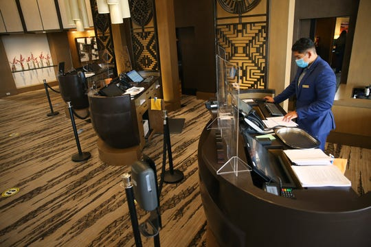 Manager Andrew Castillo works the front desk behind social distancing barriers at the Phoenician Aug 18, 2020. The resort has made changes in response to the COVID-19 outbreak.