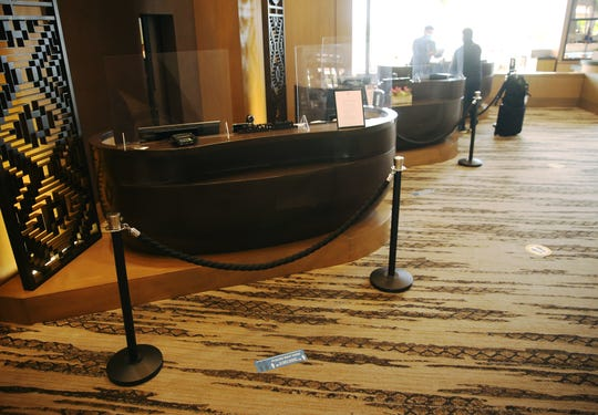 A guest is helped at the front desk as plexiglass and social distance barriers can be seen at the Phoenician Aug 18, 2020. The resort has made changes in response to the COVID-19 outbreak.