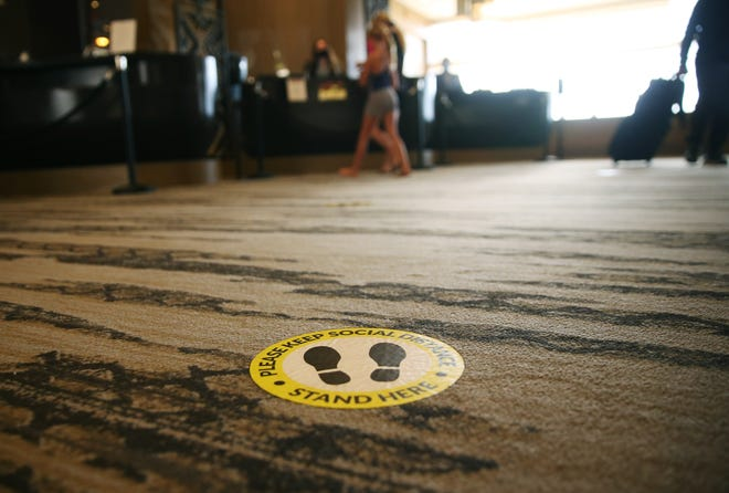 Guests are helped at the front desk as social distance reminders can be seen at the Phoenician Aug 18, 2020. The resort has made changes in response to the COVID-19 outbreak.