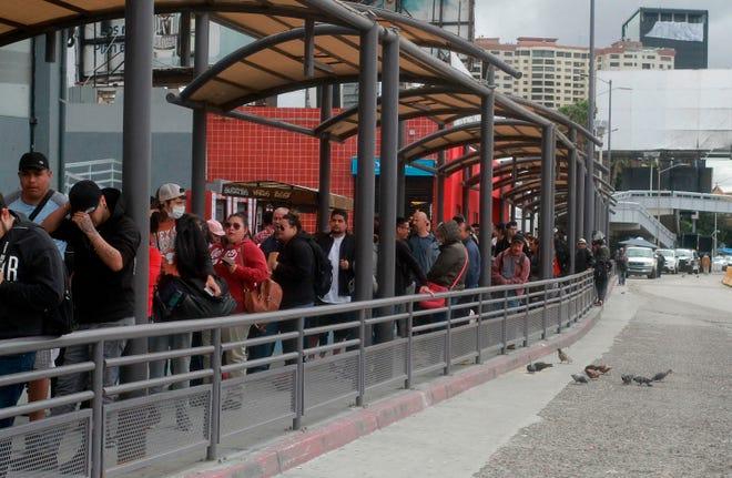 Cientos de personas hacen fila intentando cruzar hacia Estados Unidos en la frontera con México, en la ciudad de Tijuana en Baja California, (México).