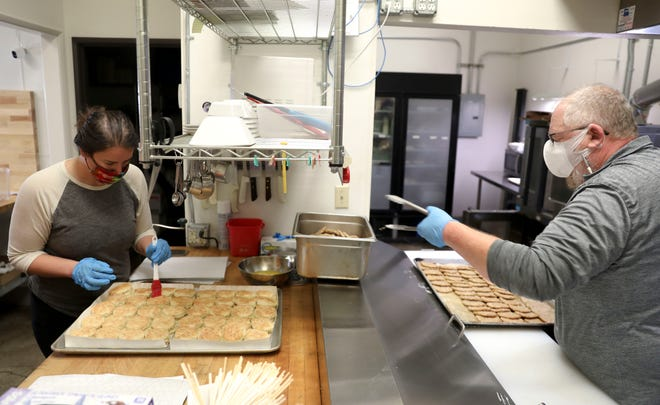Jennifer Helvie butters biscuits as Ian Croxall removes sausage patties from a sheet tray at Santiam Brewing in Salem, Oregon on Friday, Sept. 18, 2020. Amid coronavirus shutdowns limiting capacity and now shutdowns due to hazardous air quality, Santiam Brewing decided to make meals for people affected by the wildfires.