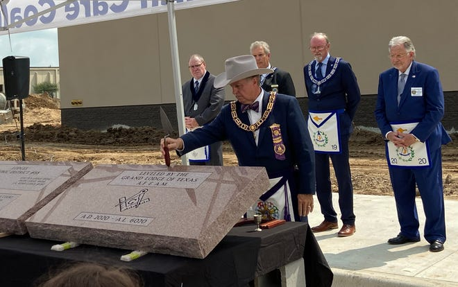 Grand Master Mason Brian Dodson uses a ceremonial trowel Friday during a cornerstone leveling ceremony for the new Wichita County LEC.