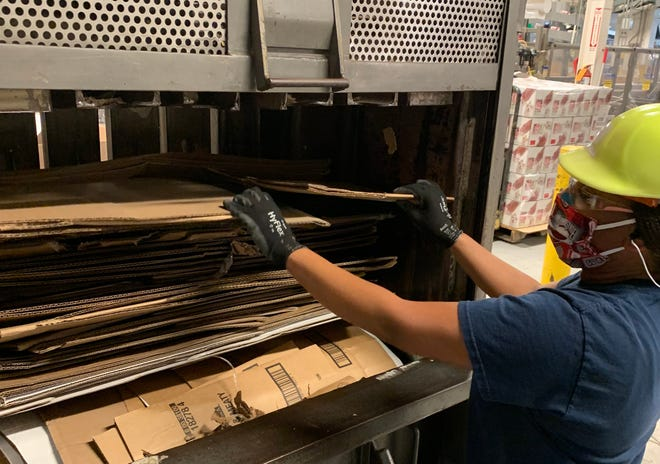 Stephanie Ford, a 12-year employee at Purina's Zanesville factory, places cardboard into a recycling baler.