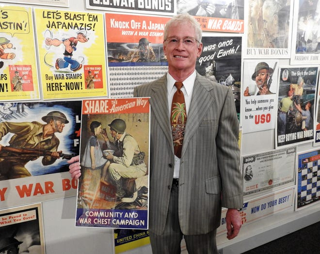 "Mike Falk of Powell with one of his favorite posters of the 511 of his collection on display at the Johnson-Humrickhouse Museum. It's done by Norman Rockwell and Falk likes the story the simple image conveys. He will be talking about 12 posters on display during the online video program ""Beyond the Artwork"" at 6 p.m. Oct. 1."