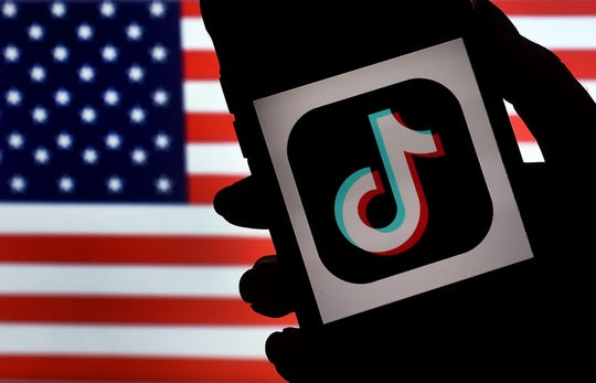 TikTok on the screen of an iPhone with the U.S. flag as background.
