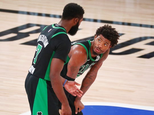 Jaylen Brown (7) and Marcus Smart (36) talk things out on the floor during the Celtics' Game 2 loss.