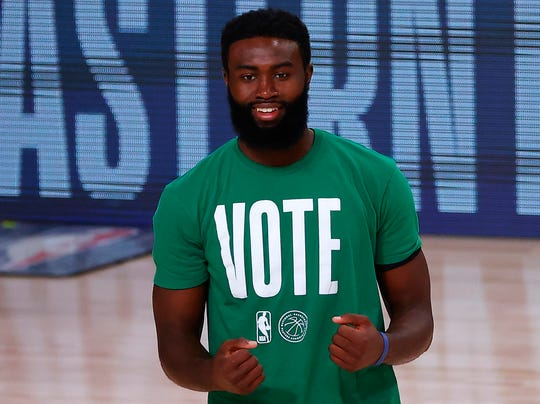 Celtics forward Jaylen Brown warms up in a VOTE shirt.
